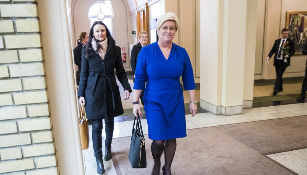 Tidligere Finansminister Siv Jensen (Frp) med Finansdepartementets kommunikasjonssjef Therese Riiser Wålen bak.