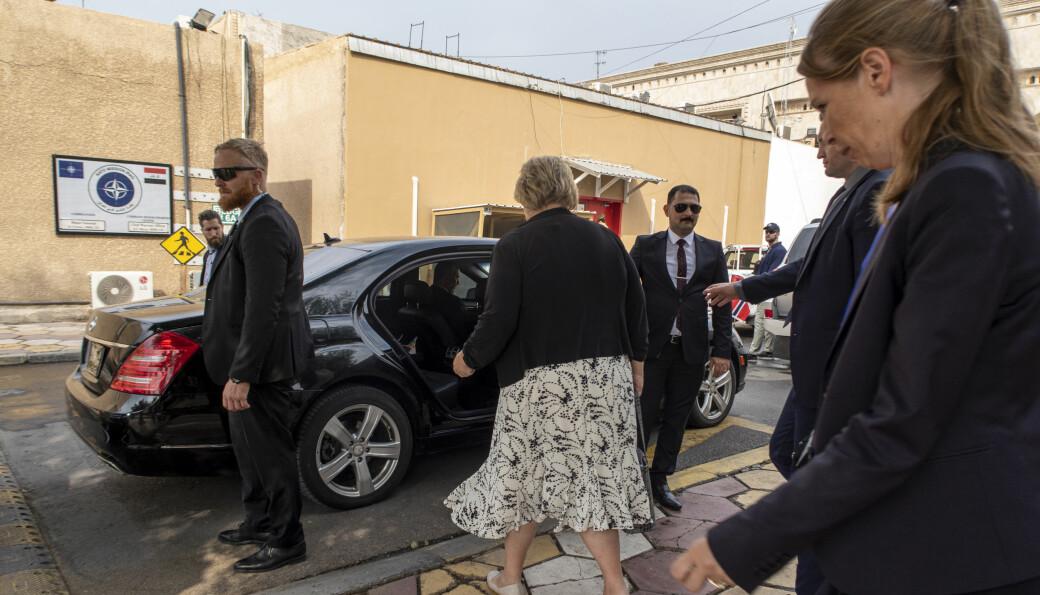 Statsminister Erna Solberg på vei inn i en trygg bil omgitt av norsk og irakisk sikkerhetspersonell. Sikkerhetsopplegget på turen var svært omfattende og PST var flere ganger kritisk til opplegget som irakiske myndigheter la opp til, kommer det fram i boken som Simon Solheim har skrevet.
