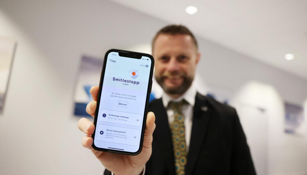 Helse- og omsorgsminister Bent Høie (H) med den nye Smittestopp-appen da den ble lansert. Det er foreløpig laber interesse for å ta den bruk.