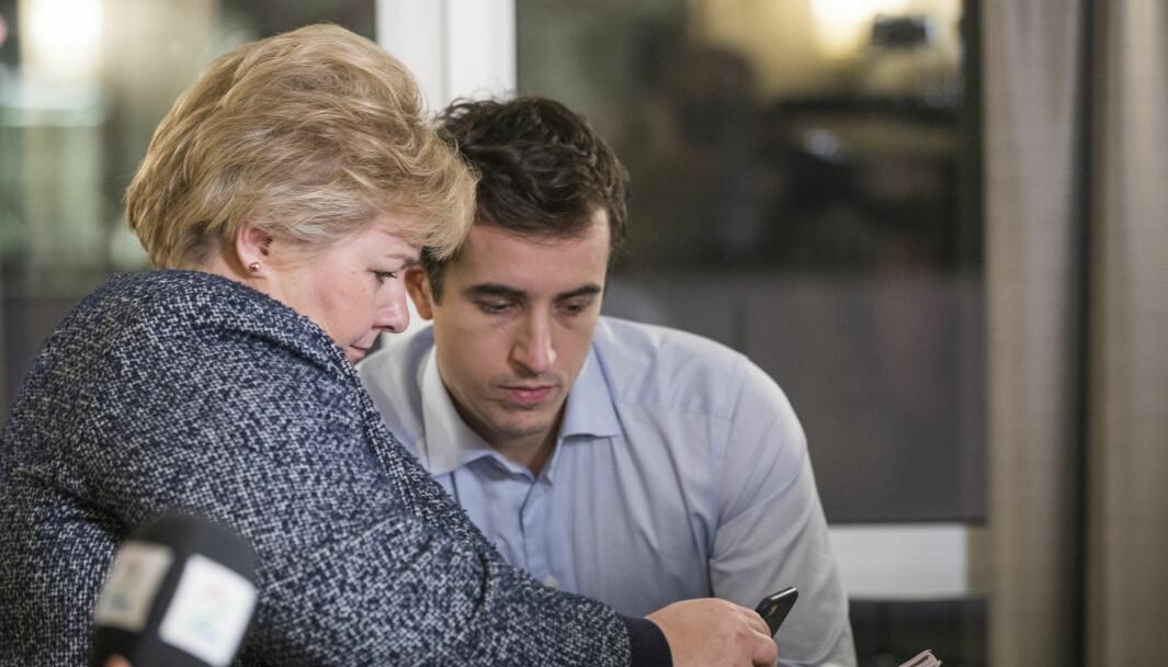 Statsminister og Høyre-leder Erna Solberg ser på mobiltelefonen til Høyres pressesjef Peder Weidemann Egseth. Foto: Håkon Mosvold Larsen / NTB