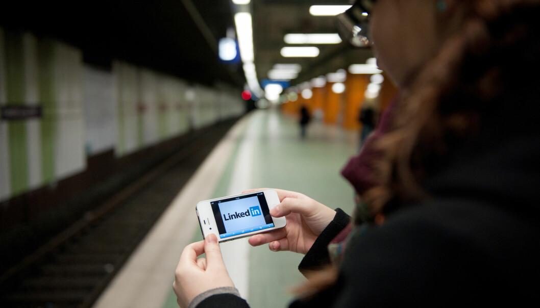 Illustrasjonsbilde: Ung kvinne sjekker LinkedIn på sin mobiltelefon. Foto: Jan Haas / NTB NB! MODELLKLARERT
