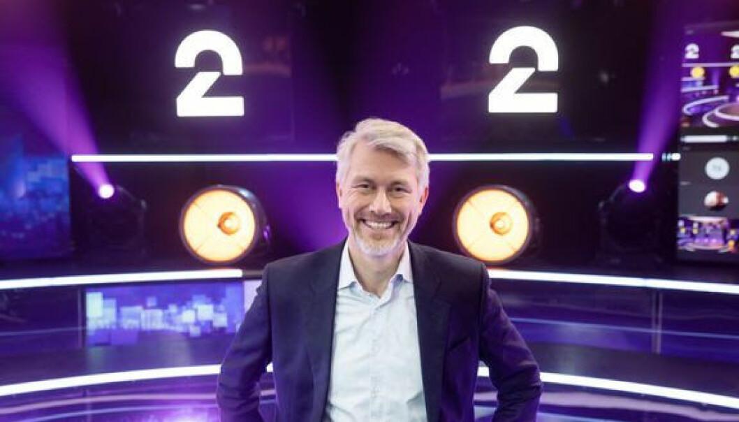 TV 2-sjef Olav T. Sandnes med TV 2 sin nye logo bak.