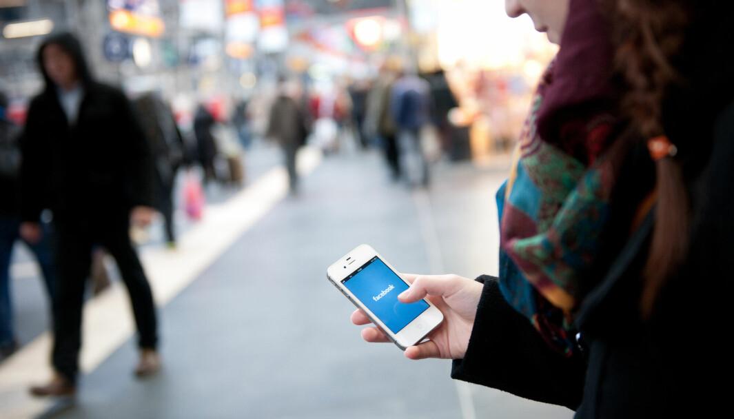 En ung kvinne sjekker Facebook på sin mobiltelefon.